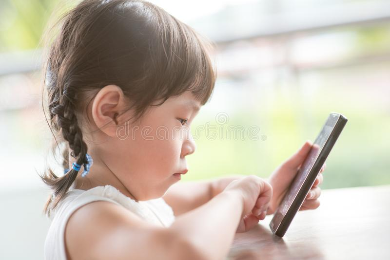 Liten flicka som använder den smarta telefonen royaltyfri foto