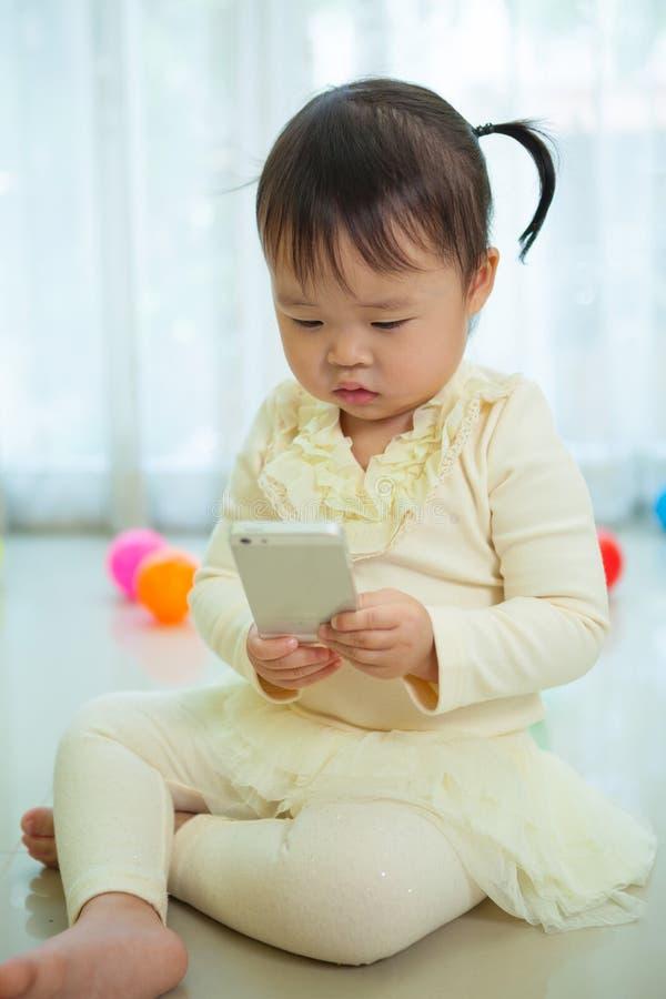 Liten flicka som använder den smarta telefonen royaltyfri fotografi