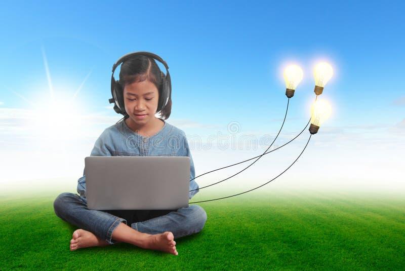 Liten flicka som använder en bärbar dator med idérika idéer för ljus kula royaltyfri fotografi