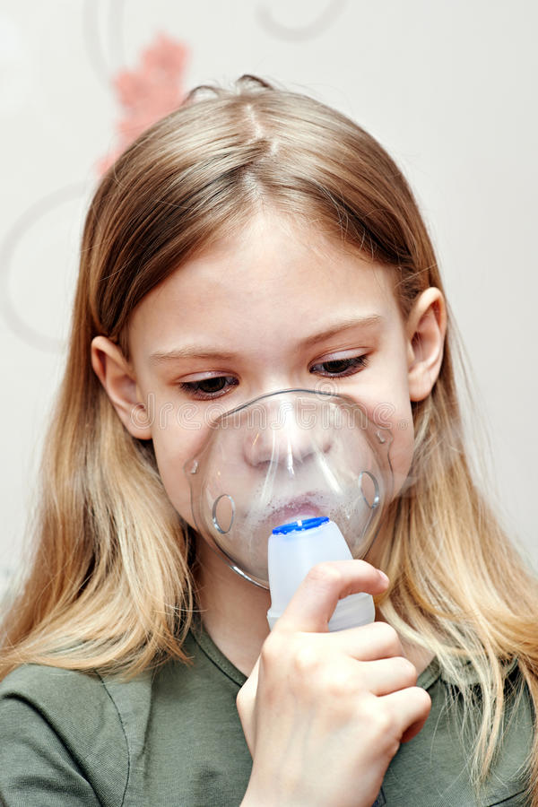 Liten flicka som använder en inhalator arkivfoto