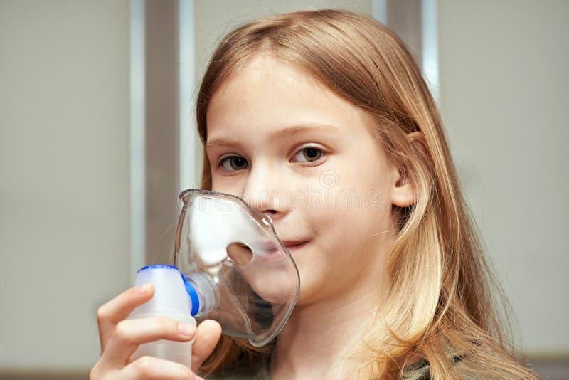 Liten flicka som använder en inhalator arkivbilder