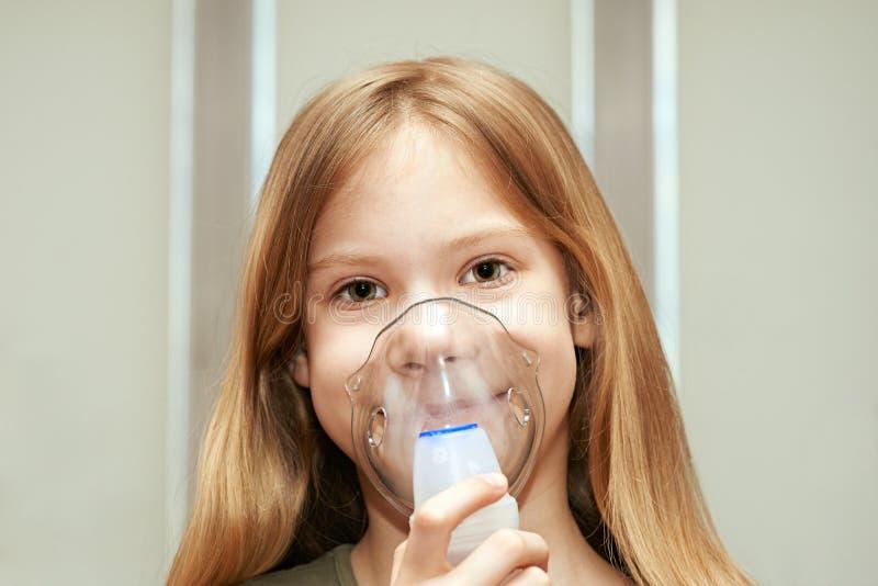 Liten flicka som använder en inhalator fotografering för bildbyråer