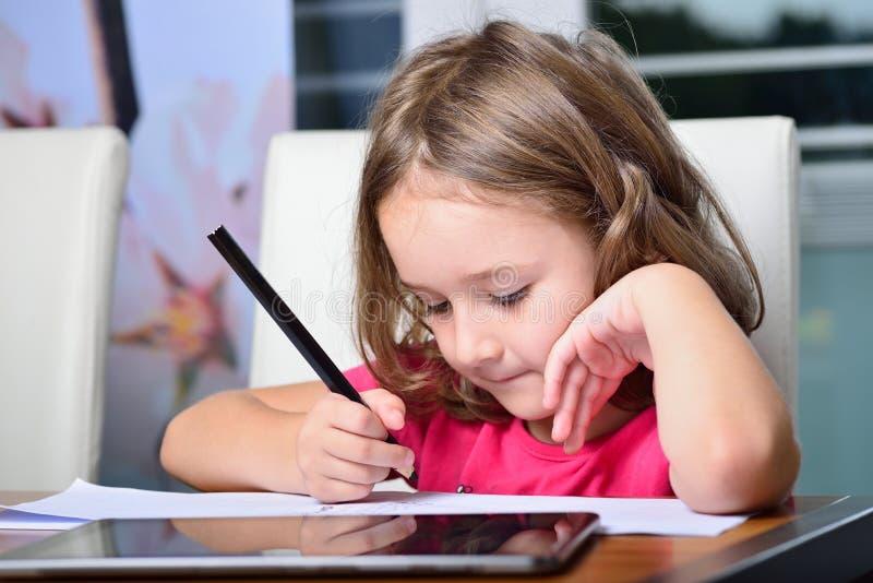 Liten flicka som använder en minnestavlaPC för läxa arkivfoto