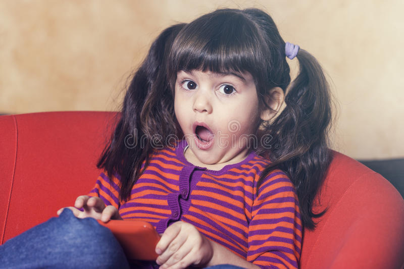 Liten flicka som använder en smartphone arkivbild