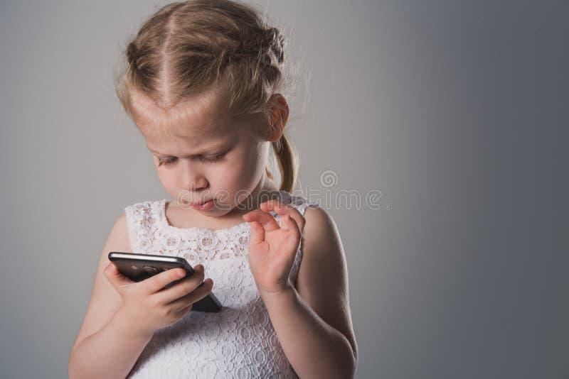 Liten flicka som använder Smartphone Närbildstående av ungen med telefonen royaltyfria foton