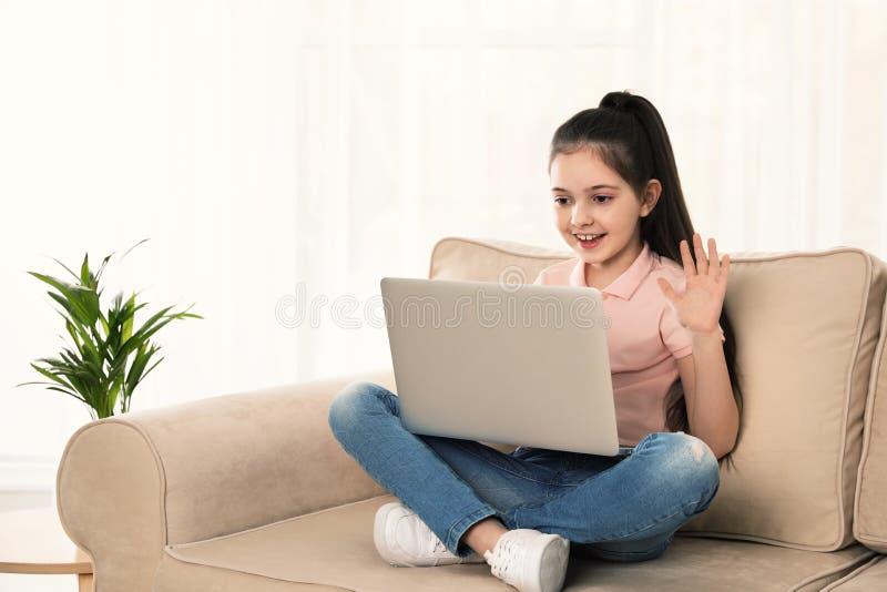 Liten flicka som anv?nder video pratstund p? b?rbara datorn royaltyfri foto