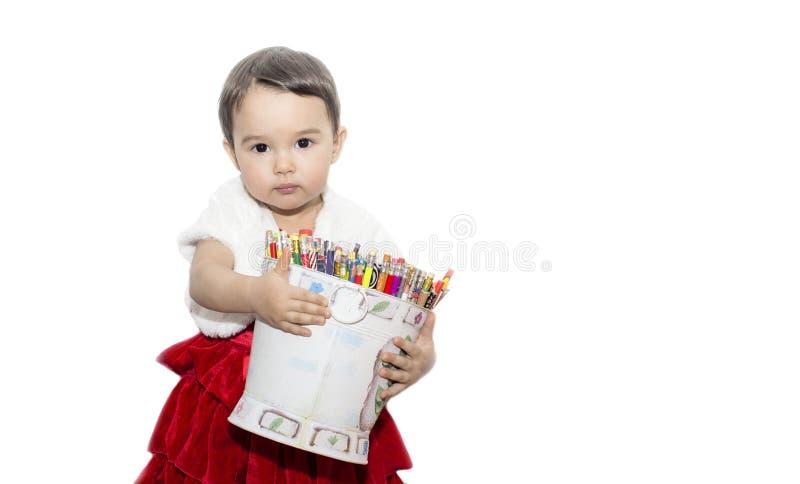 Liten flicka som bär en hink av kulöra blyertspennor royaltyfria foton