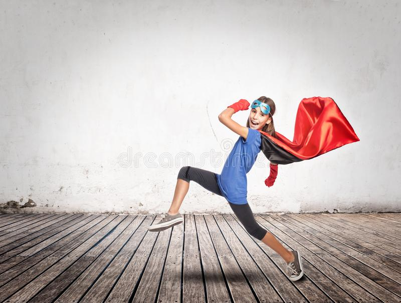 Liten flicka som bär en superherodräkt fotografering för bildbyråer