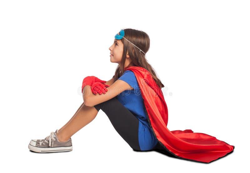 Liten flicka som bär en superherodräkt arkivfoto