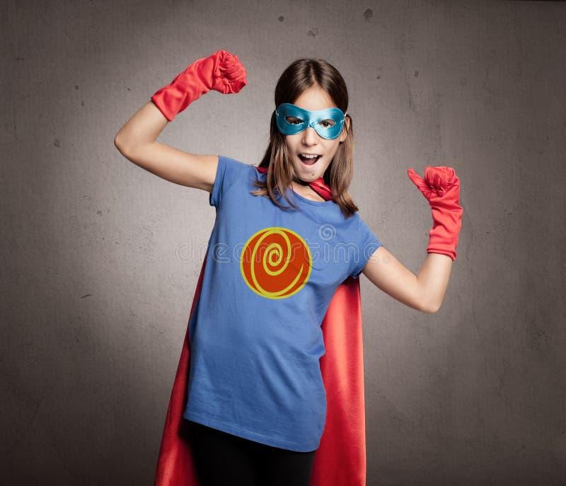 Liten flicka som bär en superherodräkt royaltyfri foto