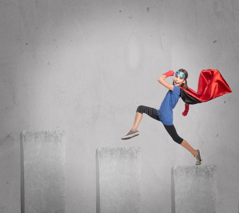 Liten flicka som bär en superherodräkt royaltyfri bild