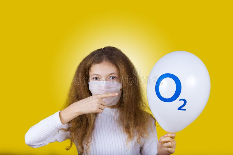 Liten flicka som bär ett maskeringsskydd på grund av förorening, poin arkivfoton