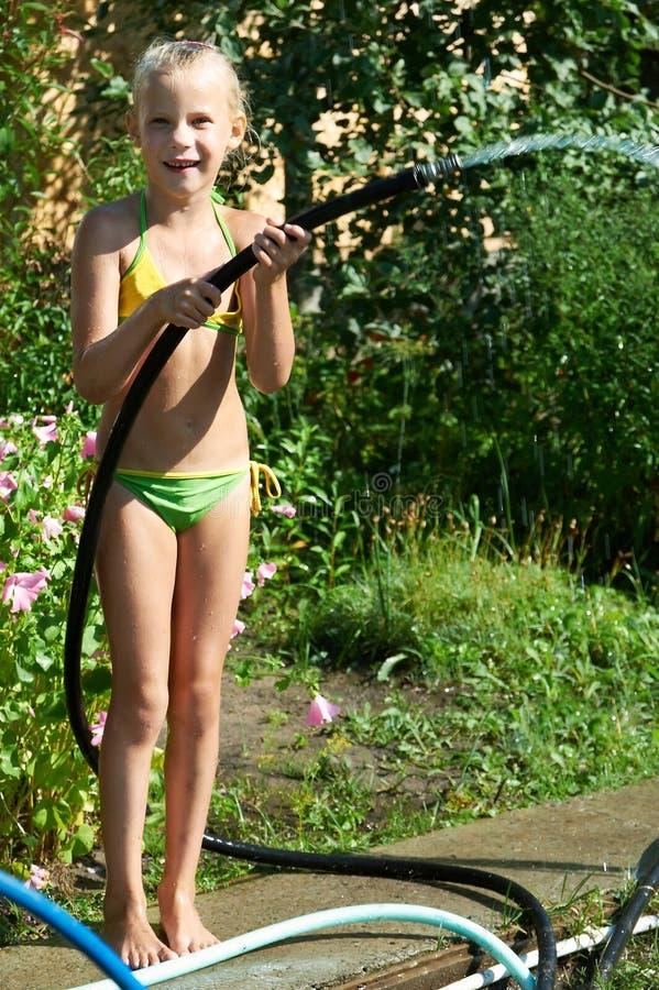 Liten flicka som bevattnar trädgården fotografering för bildbyråer