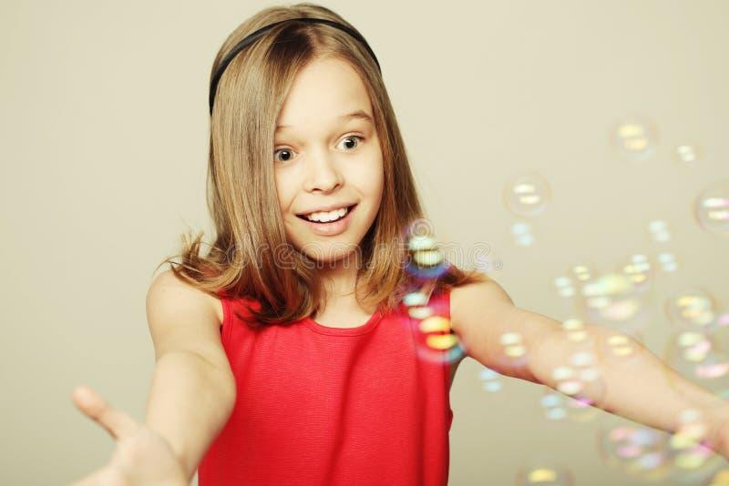 Liten flicka som blåser såpbubblor royaltyfri bild