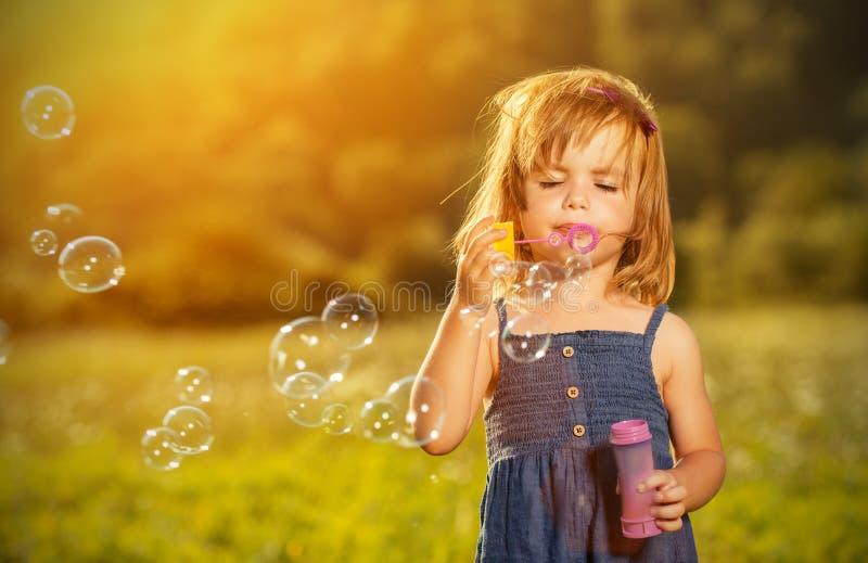 Liten flicka som blåser såpbubblor i natur royaltyfri foto