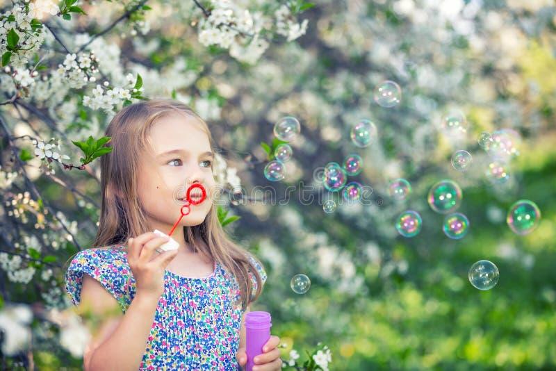 Liten flicka som blåser såpbubblor i trädgård för körsbärsröd blomning royaltyfri foto