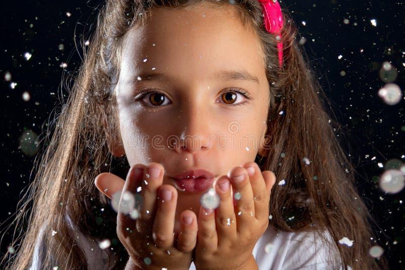 Liten flicka som blåser snö från hennes händer royaltyfri fotografi