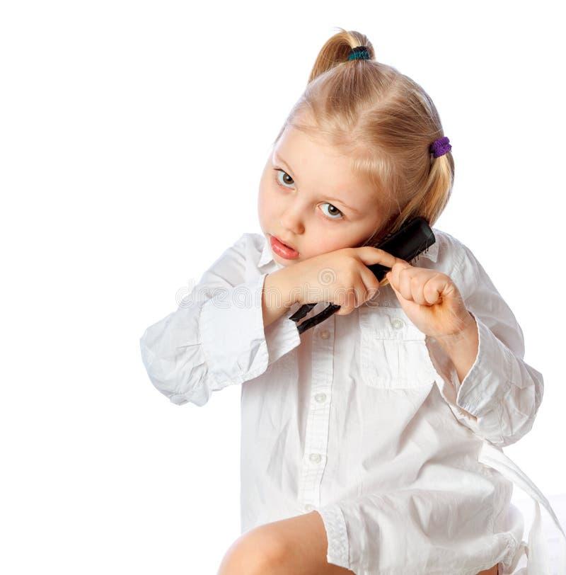 Liten flicka som borstar hennes hår, vit klänning, på en w arkivbilder