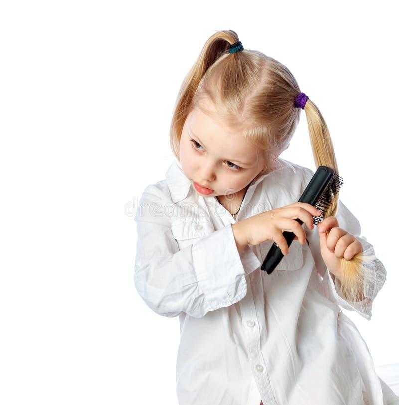 liten flicka som borstar hennes hår, vit klänning, på en w arkivfoto