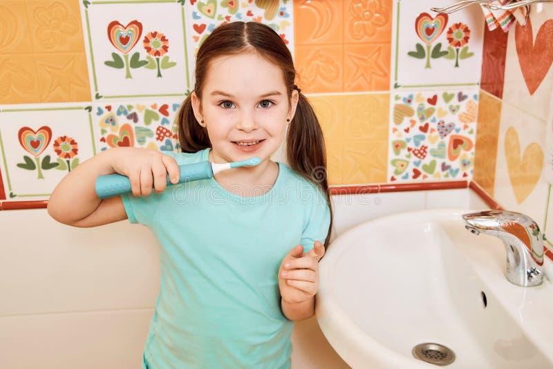 Liten flicka som borstar hennes tänder i badrummet arkivbild