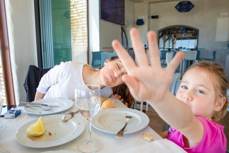 Liten flicka som döljer med handen som äter i restaurang med hennes mothe royaltyfri bild
