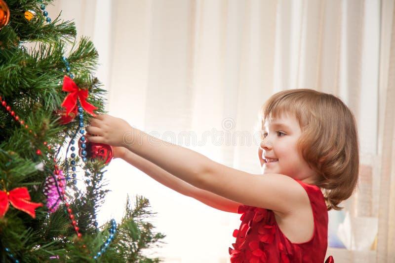 Liten flicka som dekorerar julgranen med leksaker royaltyfria bilder