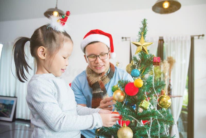Liten flicka som dekorerar julträdet med hennes fader arkivfoto