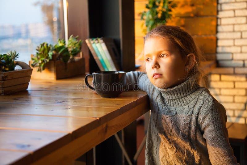 Liten flicka som drömmer med en kopp te arkivfoto