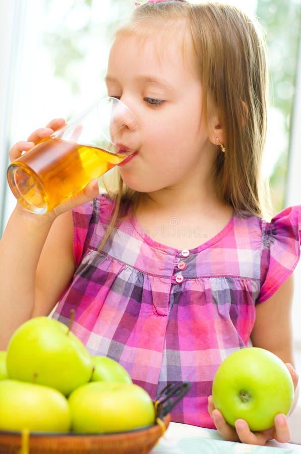 Liten flicka som dricker äppelmust arkivbilder