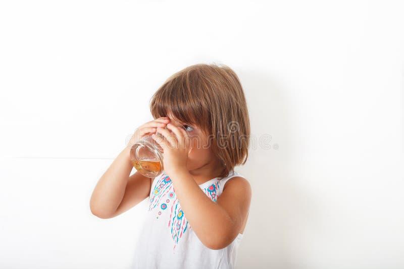 Liten flicka som dricker äppelmust från exponeringsglaset, royaltyfria bilder