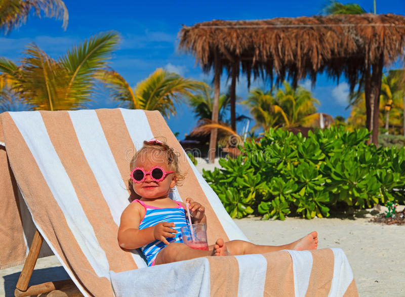 Liten flicka som dricker fruktsaft på den tropiska stranden royaltyfria foton