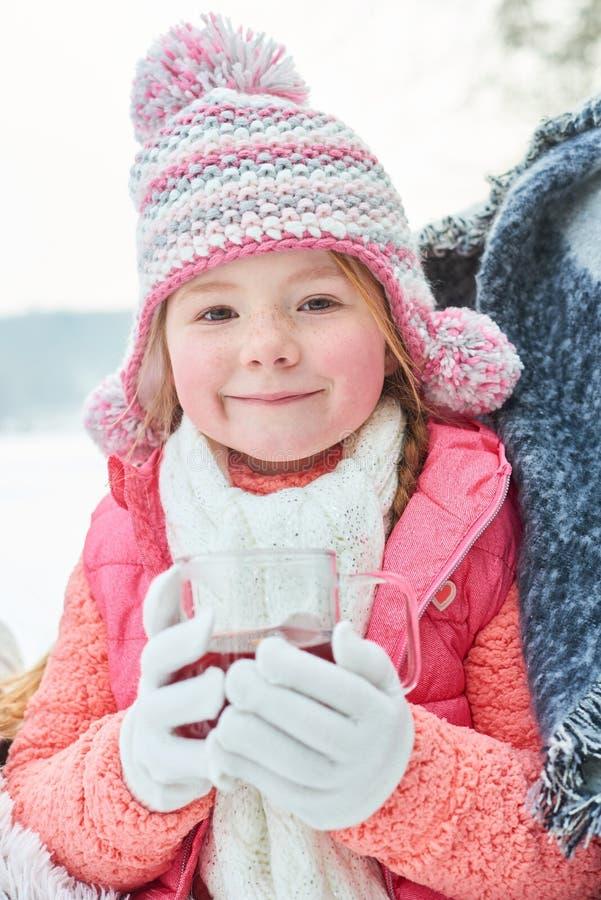 Liten flicka som dricker te i vinter royaltyfri foto