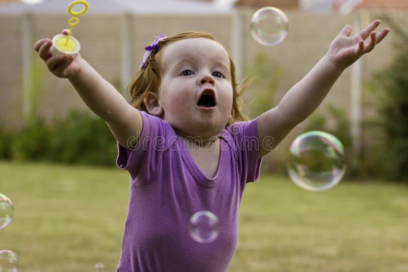 Liten flicka som fångar jaga bubblor royaltyfri bild
