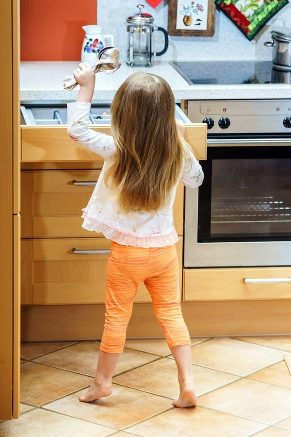 Liten flicka som får bordsservis för matställe arkivbild