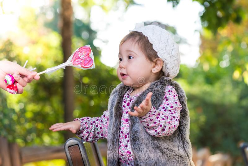 Liten flicka som får godisen från mamma royaltyfria foton
