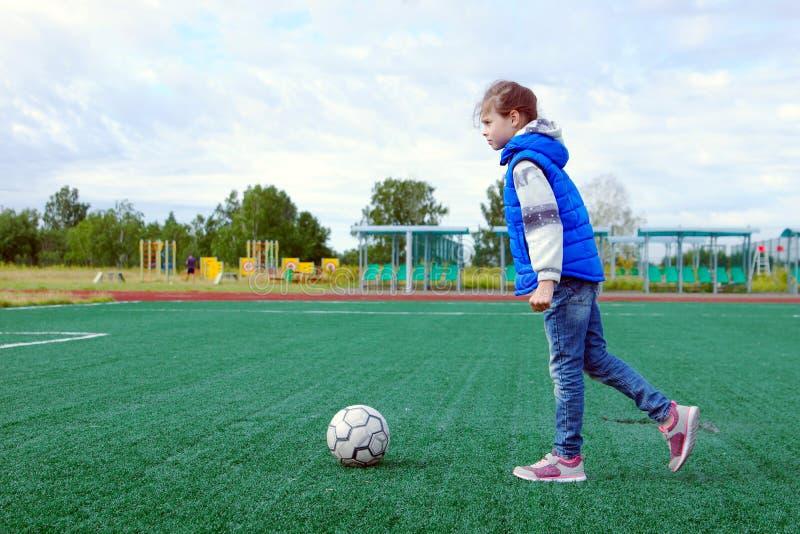 Liten flicka som förbereder sig att sparka på bollen på ett fotbollfält med utomhus- konstgjord torva arkivbilder