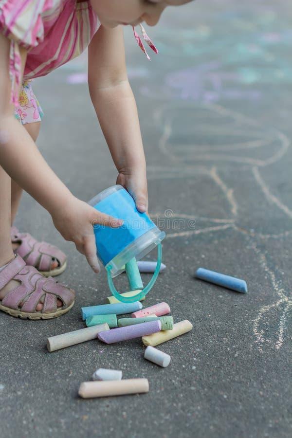 Liten flicka som förbereder sig för trottoarkritateckningen på grov asfaltbeläggningyttersida arkivfoton