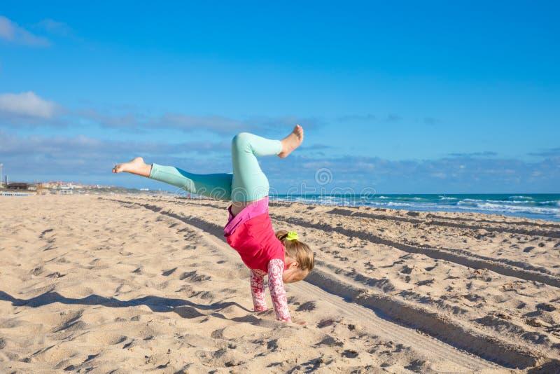 Liten flicka som försöker att göra handstans på La Barrosa för sandig strand royaltyfria foton