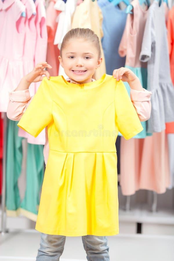 Liten flicka som försöker en ny klänning arkivbild