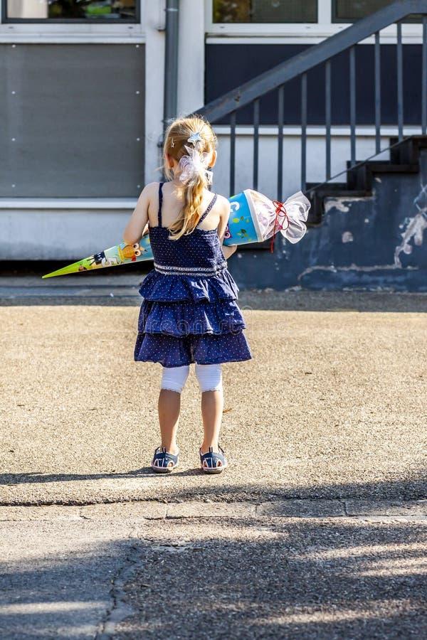 Liten flicka som framme står av skolabyggnaden som rymmer hennes godiskotte arkivfoto