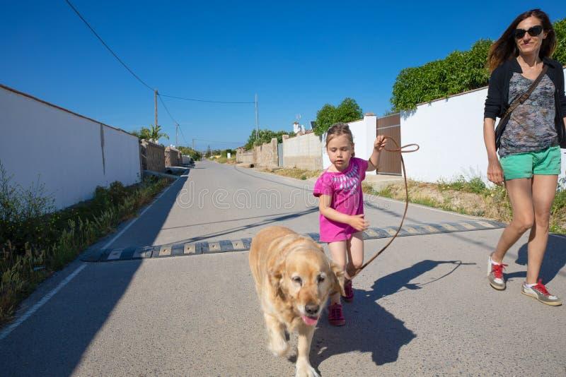 Liten flicka som går en hund bredvid kvinna i mitt av gatan arkivfoton