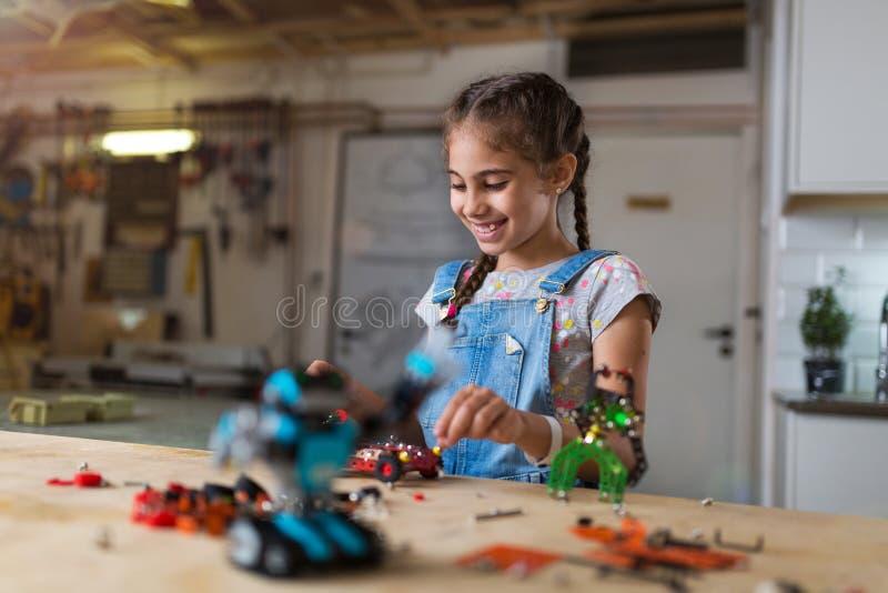 Liten flicka som gör en robot royaltyfri foto