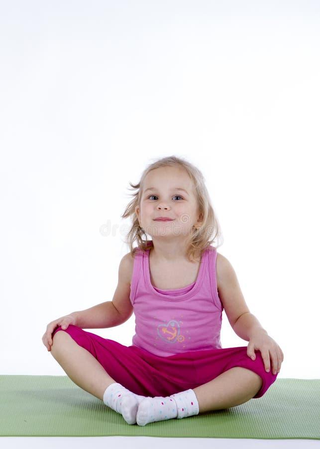 Liten flicka som gör gymnastiska övningar på det mattt arkivfoto
