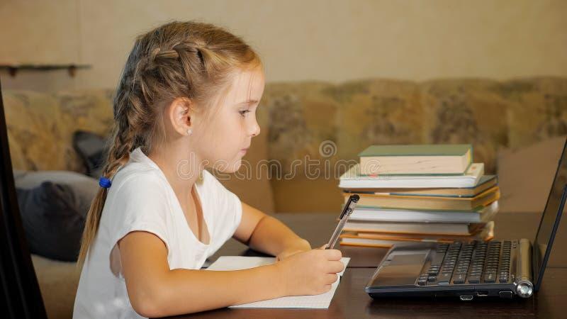 Liten flicka som gör läxa med bärbara datorn royaltyfri fotografi