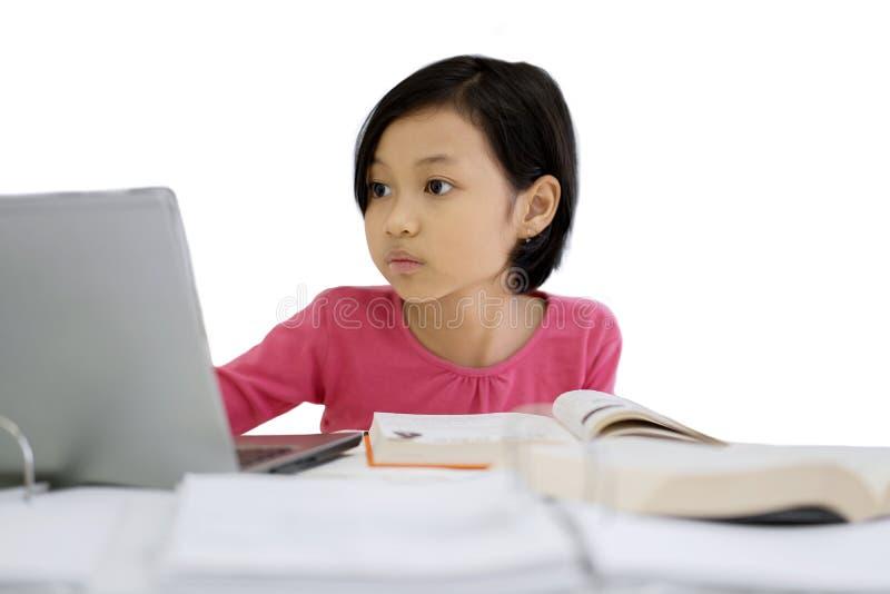 Liten flicka som gör läxa med en bärbar dator på studio royaltyfria foton