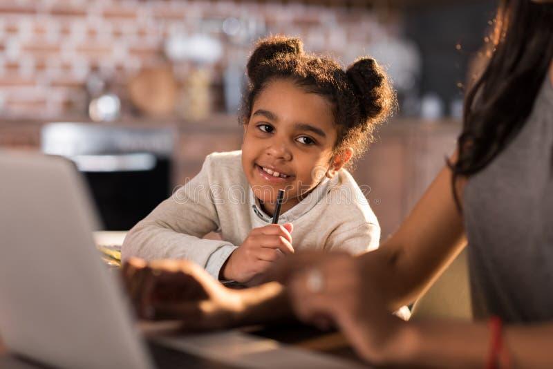 Liten flicka som gör läxa med modern som nära använder bärbara datorn förbi royaltyfri bild