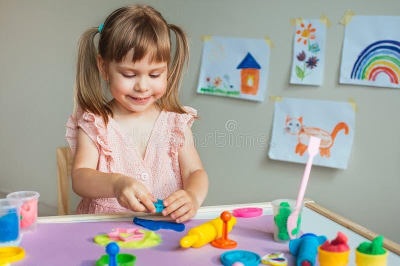 Liten flicka som gjuter färgrik lera på tabellen royaltyfria bilder