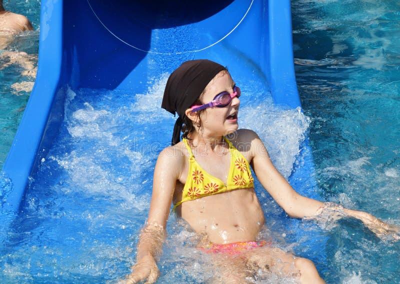 Liten flicka som glider i vattenglidbanan under semester i sommer royaltyfri bild