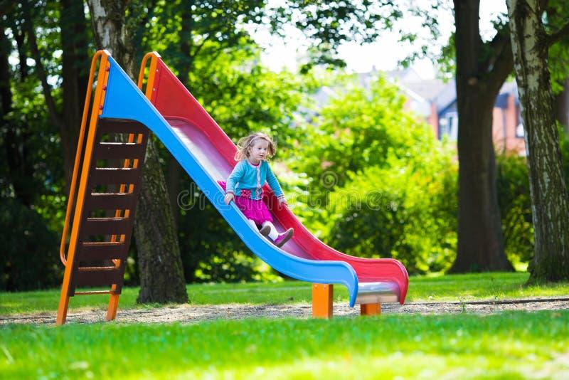 Liten flicka som glider på en lekplats fotografering för bildbyråer