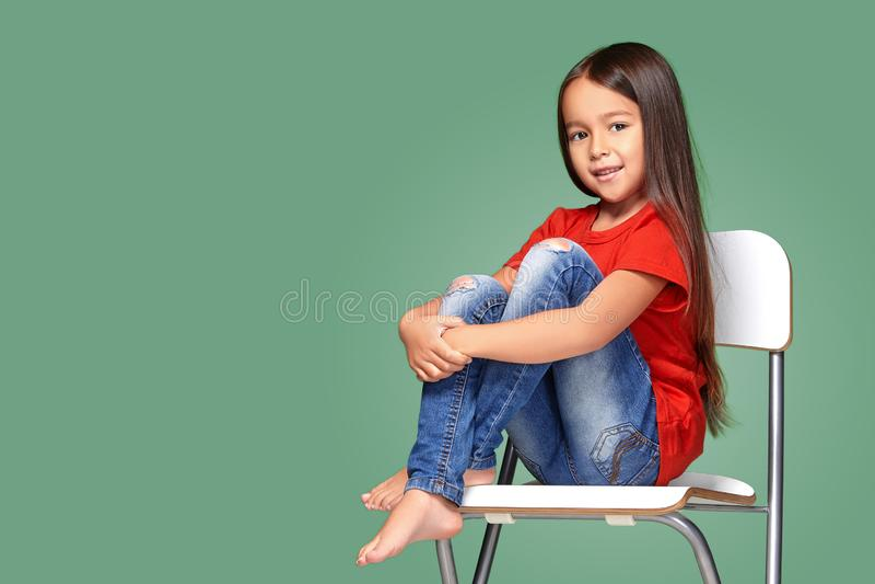 Liten flicka som ha på sig den röda t-kort stavelse och poserar på stol arkivfoton